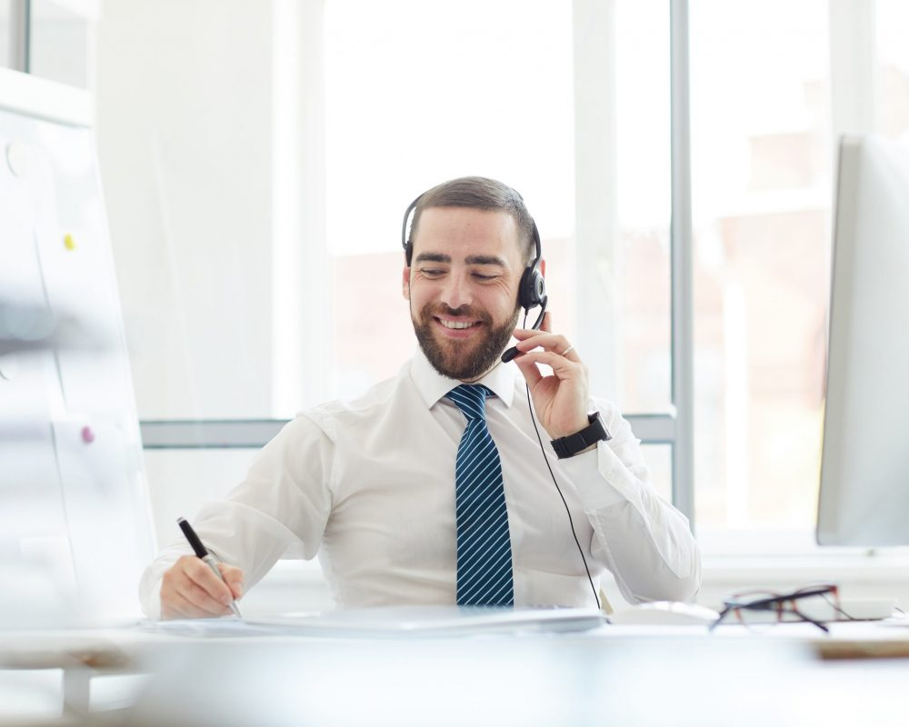Positive communicative handsome young call center agent sitting at table and making notes in notepad while talking to customer via headset